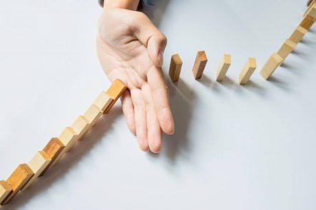 Immagine di una mano che ferma il domino